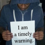 "Young man holding ""I am a timely warning"" sign"