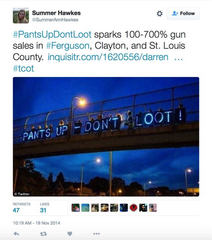 "Screenshot of a tweet reading, ""#PantsUpDontLoot sparks 100-700% gun sales in #Ferguson, Clayton, and St. Louis County,"" containing an image of a light-up blue sign above a bridge reading: HANDS UP - DON'T SHOOT! (Hawkes)"