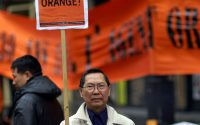 Man holding sign protesting agent orange