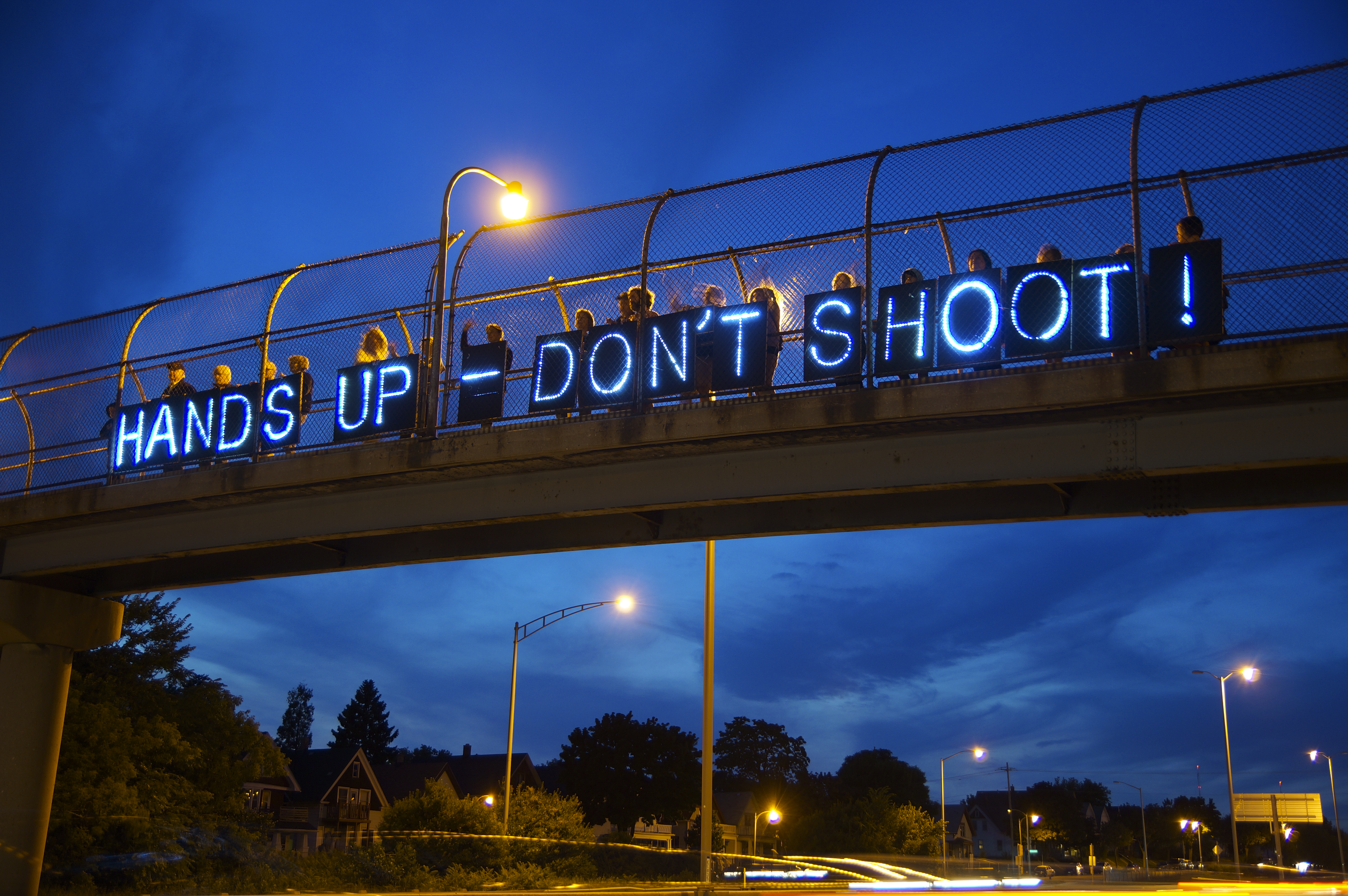 "Photograph of ""Hands up, Don't Shoot"" sign on bridge"