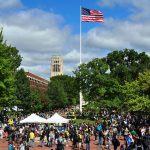 University of Michigan Diag during Festifall in September 2010. Image shows a large crowd gathered and an American flag in the center of the photo.